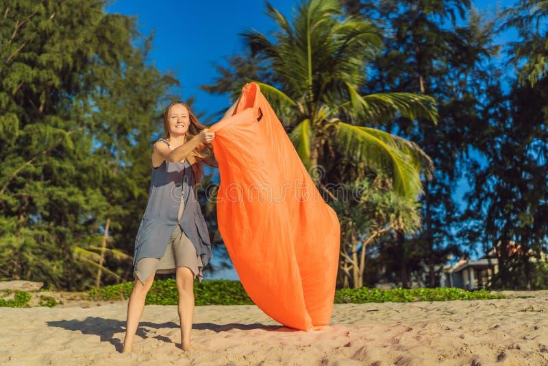 Il ritratto di stile di vita dell'estate della donna gonfia un sofà arancio gonfiabile sulla spiaggia dell'isola tropicale Rilass fotografia stock libera da diritti