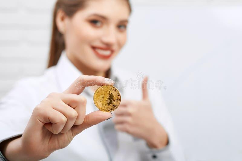 Il ritratto di un codice di abbigliamento d'uso della donna di affari tiene il bitcoin dorato immagini stock libere da diritti