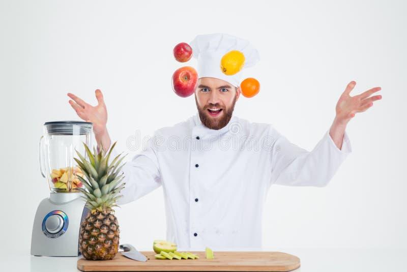 Il ritratto di un cuoco maschio hapy del cuoco unico manipola con i frutti immagini stock