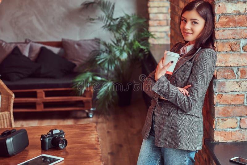 Il ritratto di un fotografo della ragazza si è vestito in un rivestimento elegante grigio che tiene la tazza di caffè asportabile immagini stock libere da diritti
