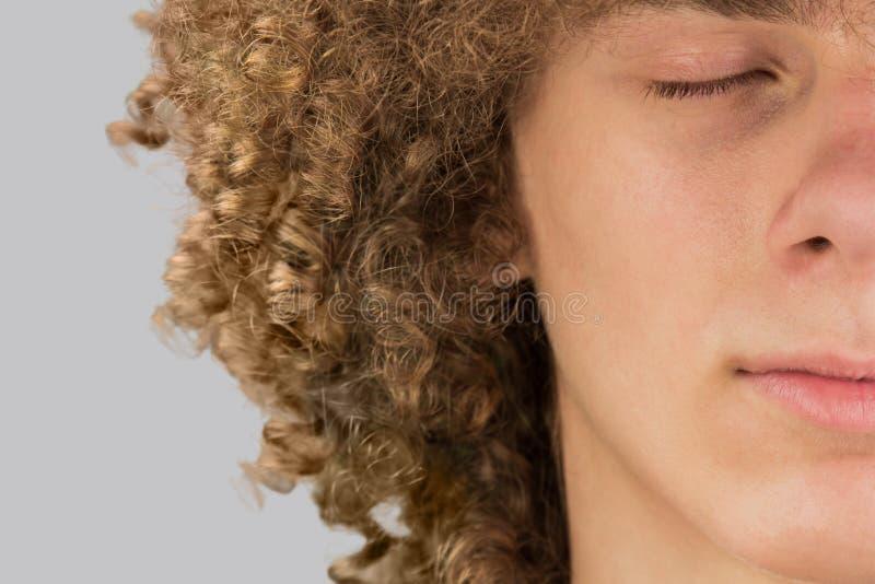Il ritratto di un giovane europeo riccio con i capelli ricci lunghi e gli occhi chiusi è diviso in due parti. capelli molto lisci fotografia stock libera da diritti