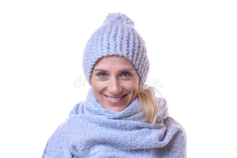Il ritratto di un inverno d'uso sorridente della donna copre immagine stock libera da diritti