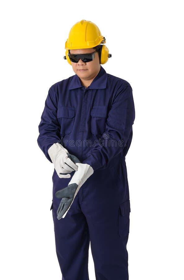 Il ritratto di un lavoratore in meccanico Jumpsuit sta rimuovendo i guanti isolati su fondo bianco fotografia stock libera da diritti