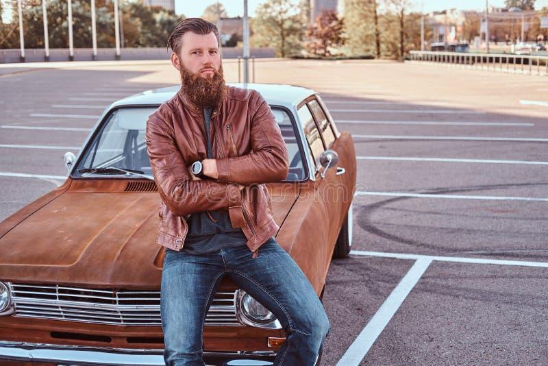Il ritratto di un maschio barbuto alla moda in vestiti antiquati si siede sulla retro automobile del cappuccio nel parcheggio del fotografia stock libera da diritti
