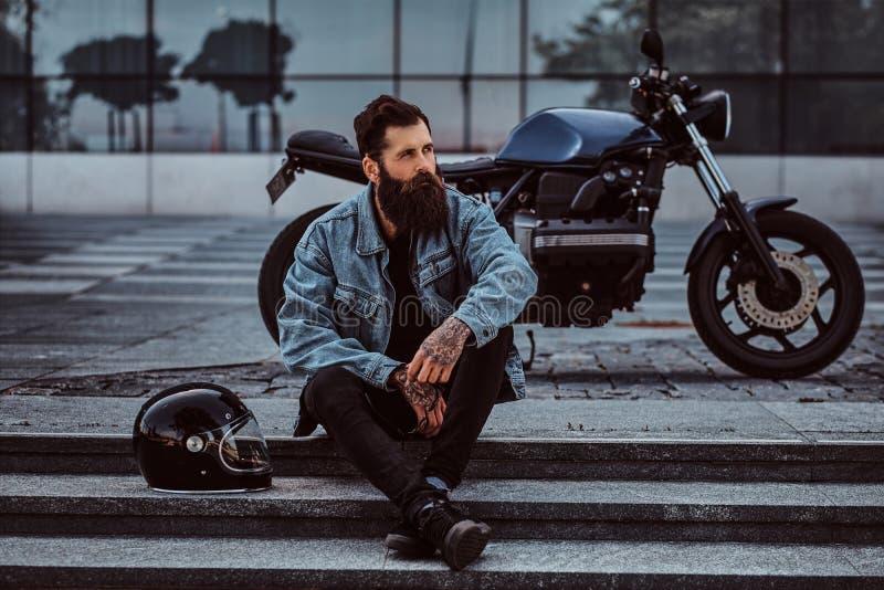 Il ritratto di un maschio barbuto brutale si è vestito in un rivestimento dei jeans che si siede sui punti vicino al suo retro mo immagini stock libere da diritti