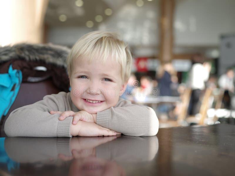Il ritratto di un ragazzino sorridente si siede ad una tavola fotografia stock libera da diritti