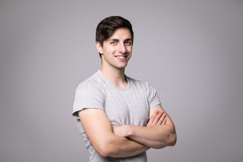 Il ritratto di un uomo casuale felice che sta con le armi ha ripiegato il fondo grigio e l'esame della macchina fotografica immagini stock libere da diritti
