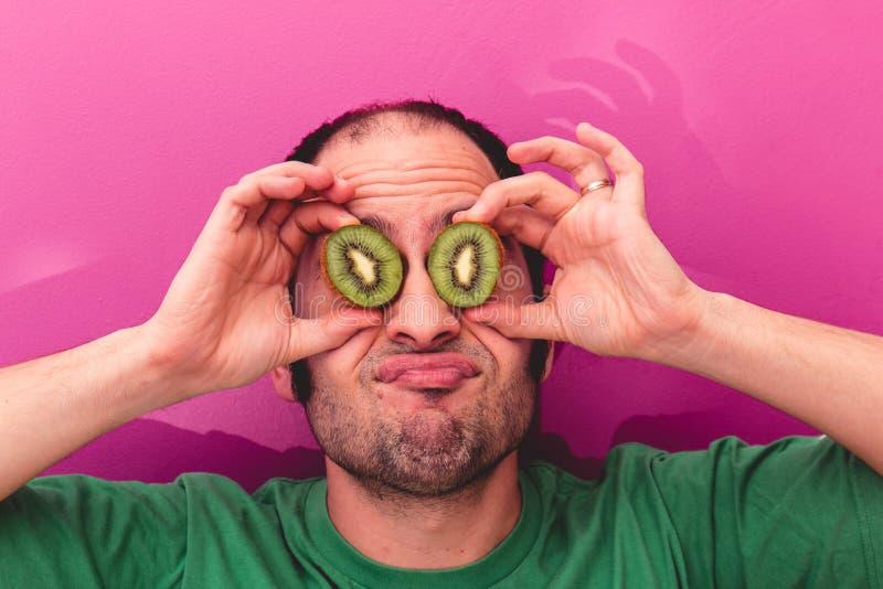 Il ritratto di un uomo che tiene due ha affettato i kiwi nei suoi occhi fotografie stock libere da diritti