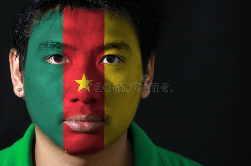 Il ritratto di un uomo con la bandiera del Camerun ha dipinto sul suo fronte su fondo nero immagine stock libera da diritti