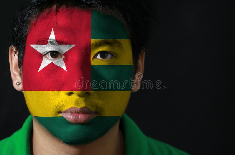 Il ritratto di un uomo con la bandiera del Togo ha dipinto sul suo fronte su fondo nero immagini stock libere da diritti