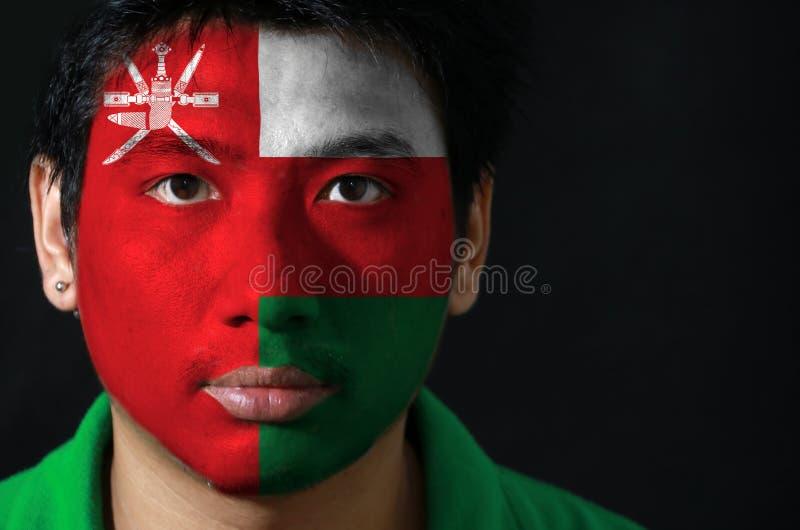 Il ritratto di un uomo con la bandiera dell'Oman ha dipinto sul suo fronte su fondo nero immagine stock libera da diritti