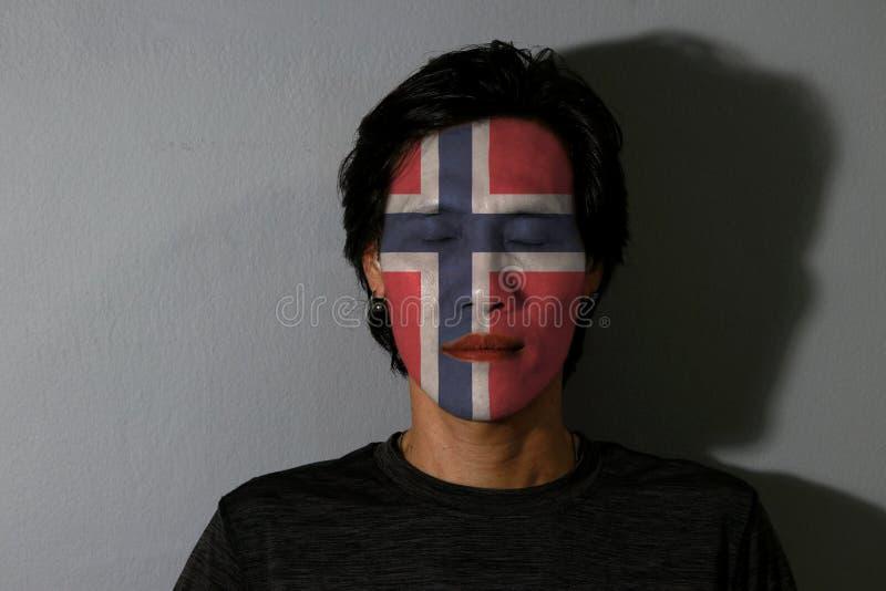 Il ritratto di un uomo con la bandiera della Norvegia ha dipinto sul suoi fronte ed occhi vicini con ombra nera su fondo grigio fotografia stock libera da diritti