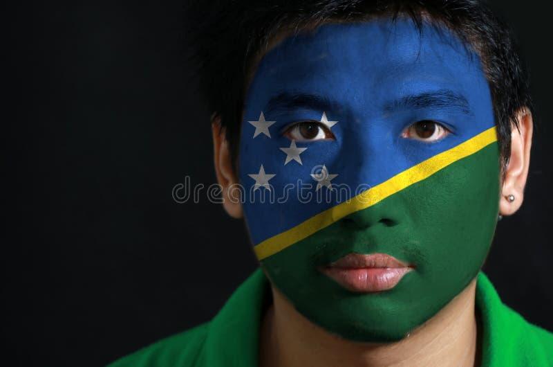 Il ritratto di un uomo con la bandiera di Solomon Islands ha dipinto sul suo fronte su fondo nero immagine stock libera da diritti