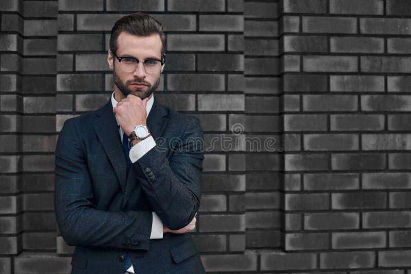 Il ritratto di un uomo d'affari bello sorridente con le armi ha ripiegato immagini stock