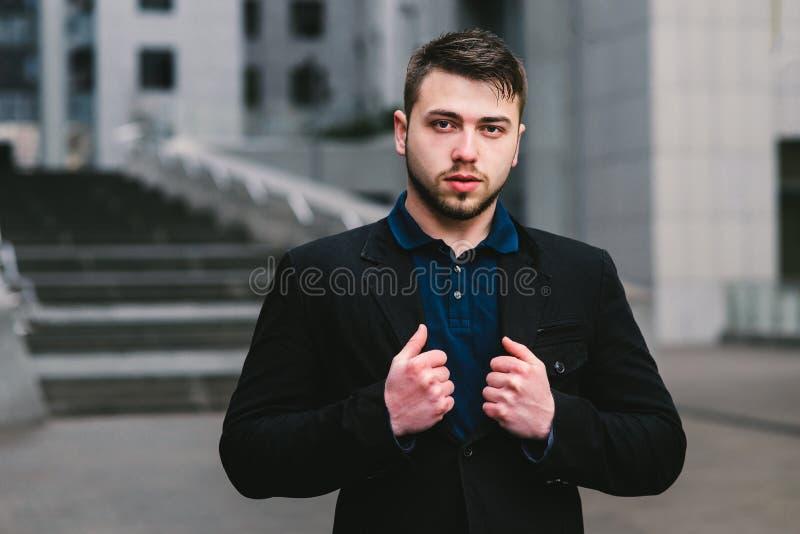 Il ritratto di un uomo d'affari serio dell'uomo corregge quel vestito sui precedenti del paesaggio urbano immagini stock libere da diritti