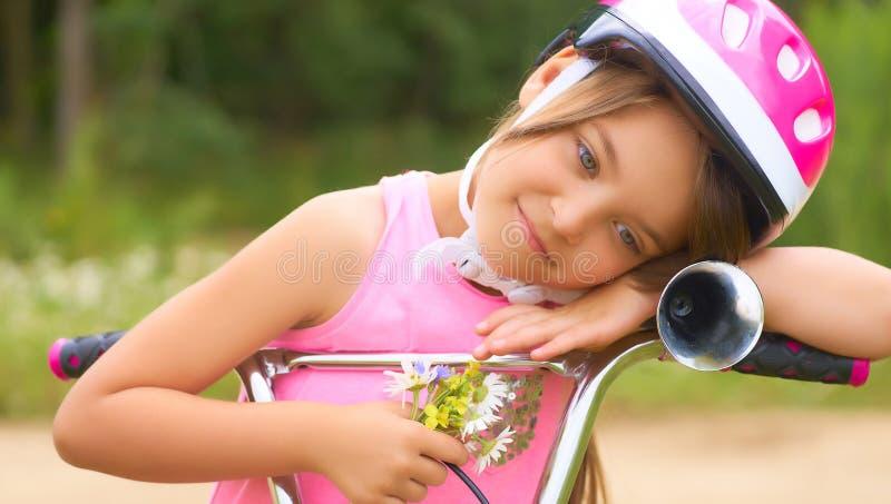 Il ritratto di una bambina in un casco protettivo controlla la sua bici e tiene un mazzo delle margherite immagini stock