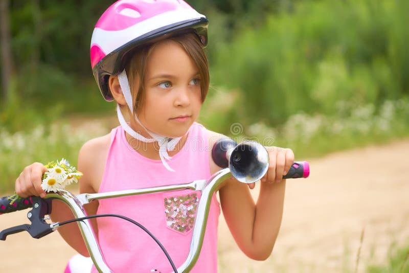 Il ritratto di una bambina in un casco protettivo controlla la sua bici e tiene un mazzo delle margherite immagine stock