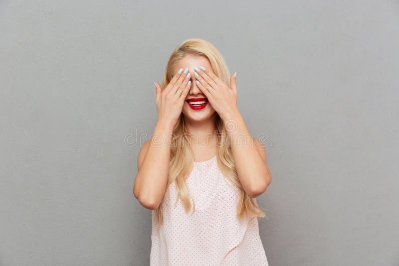 Il ritratto di una copertura felice della donna osserva con le mani immagini stock