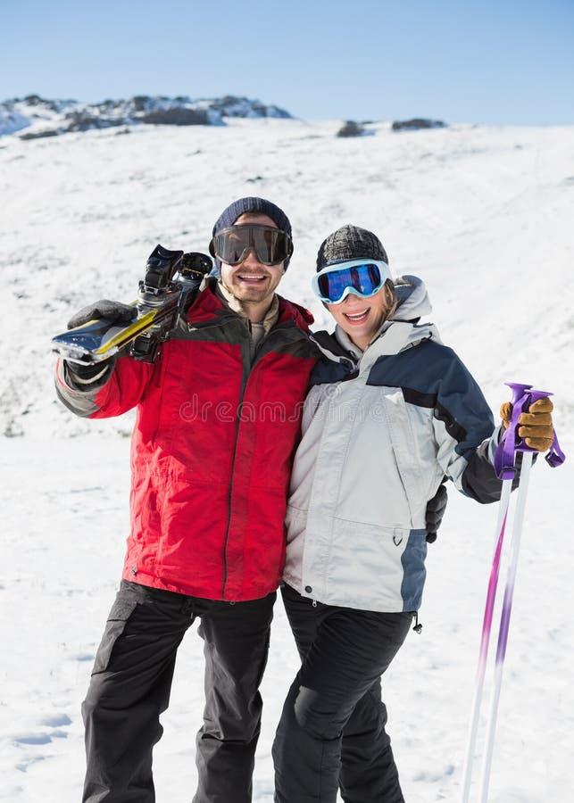 Il ritratto di una coppia allegra con lo sci imbarca su neve immagini stock