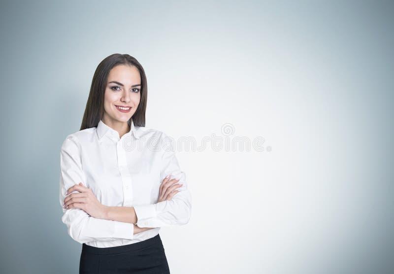 Il ritratto di una donna di affari sorridente che sta con le sue armi ha attraversato vicino ad una parete grigia e ad esaminare  fotografia stock libera da diritti