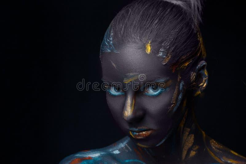 Il ritratto di una giovane donna che sta posando ha coperto di pittura nera fotografia stock libera da diritti
