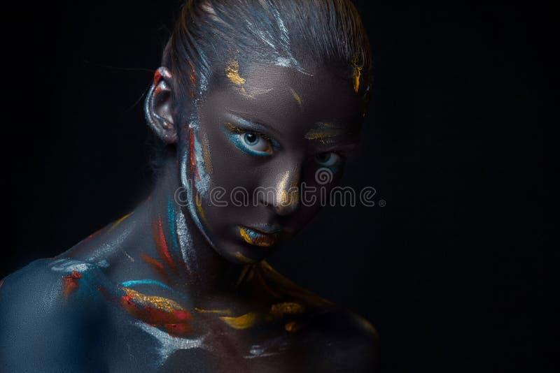 Il ritratto di una giovane donna che sta posando ha coperto di pittura nera immagine stock