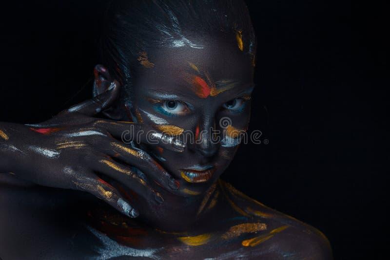 Il ritratto di una giovane donna che sta posando ha coperto di pittura nera immagini stock