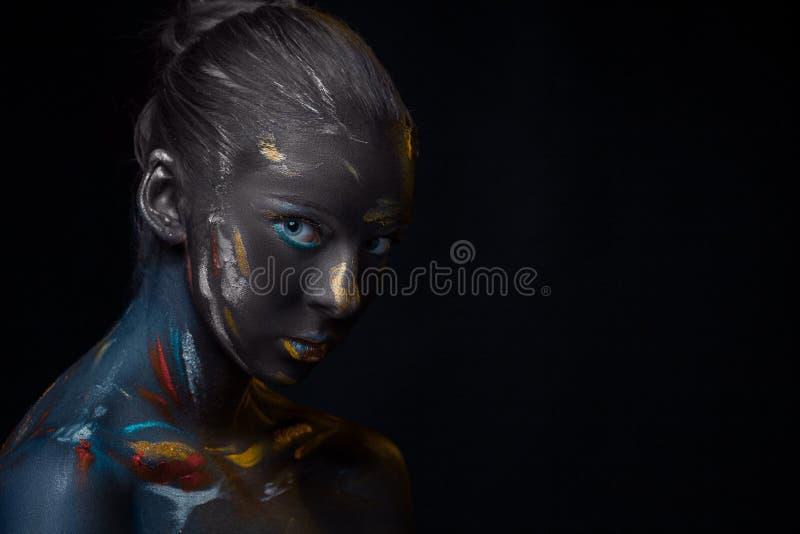 Il ritratto di una giovane donna che sta posando ha coperto di pittura nera immagine stock libera da diritti