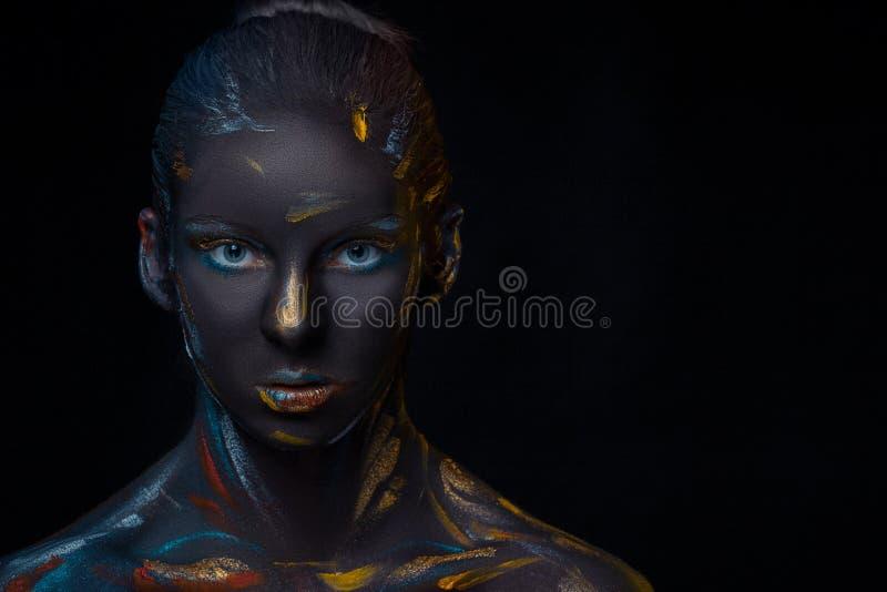 Il ritratto di una giovane donna che sta posando ha coperto di pittura nera fotografia stock
