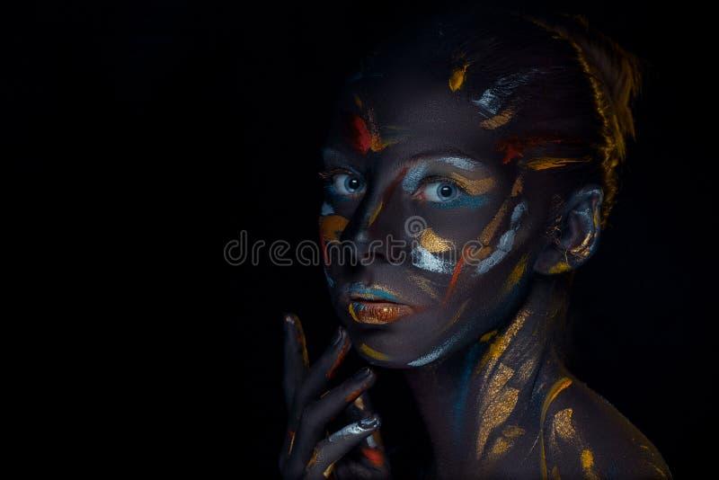 Il ritratto di una giovane donna che sta posando ha coperto di pittura nera immagini stock libere da diritti