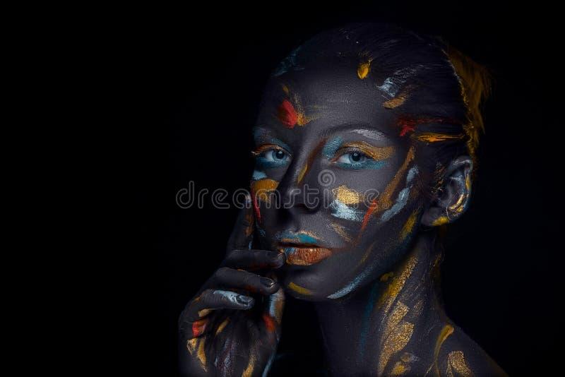 Il ritratto di una giovane donna che sta posando ha coperto di pittura nera fotografie stock
