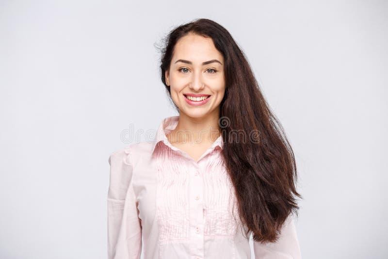 Il ritratto di una giovane donna con un sorriso, i capelli neri e un marrone a trentadue denti affascinanti osserva su un fondo b immagini stock