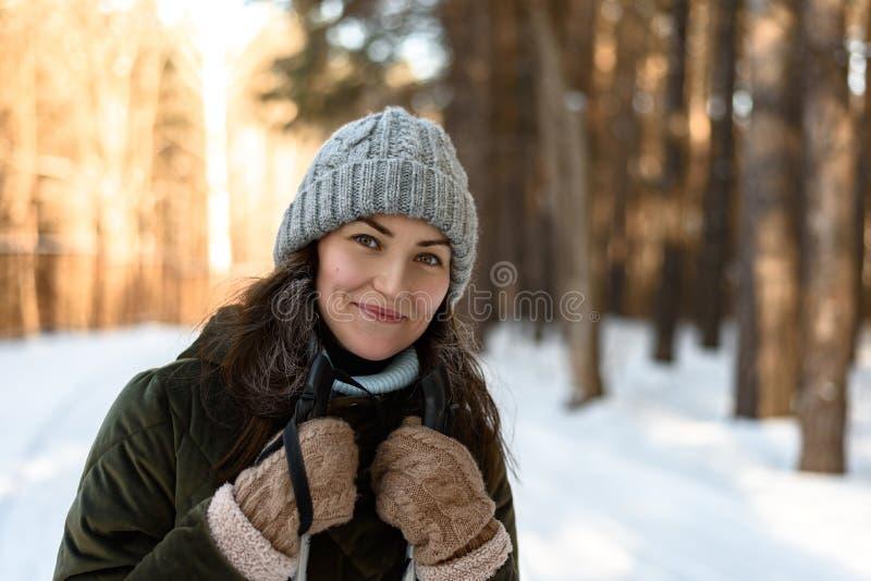 Il ritratto di una giovane donna in vestiti dell'inverno nella donna della foresta A dell'inverno sta sciando nell'inverno nella  immagine stock