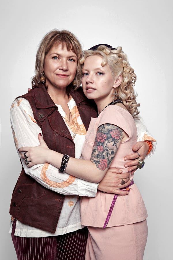 Il ritratto di una madre anziana d'abbraccio e di una figlia adulta si è vestito in bei vestiti nel retro stile immagini stock libere da diritti