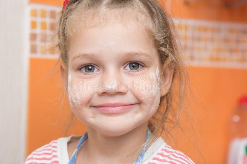 Il ritratto di una ragazza allegra con un fronte ha macchiato con farina immagini stock libere da diritti