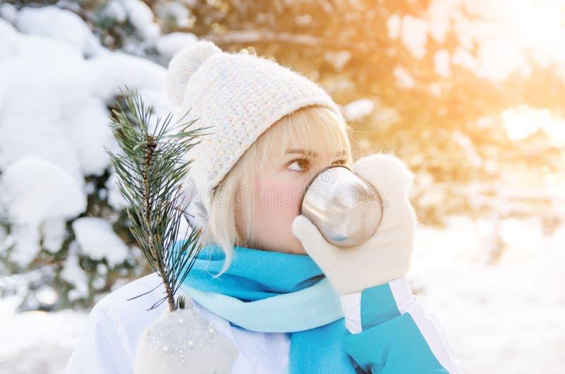 Il ritratto di una ragazza bionda attraente beve il tè caldo da una tazza fotografia stock