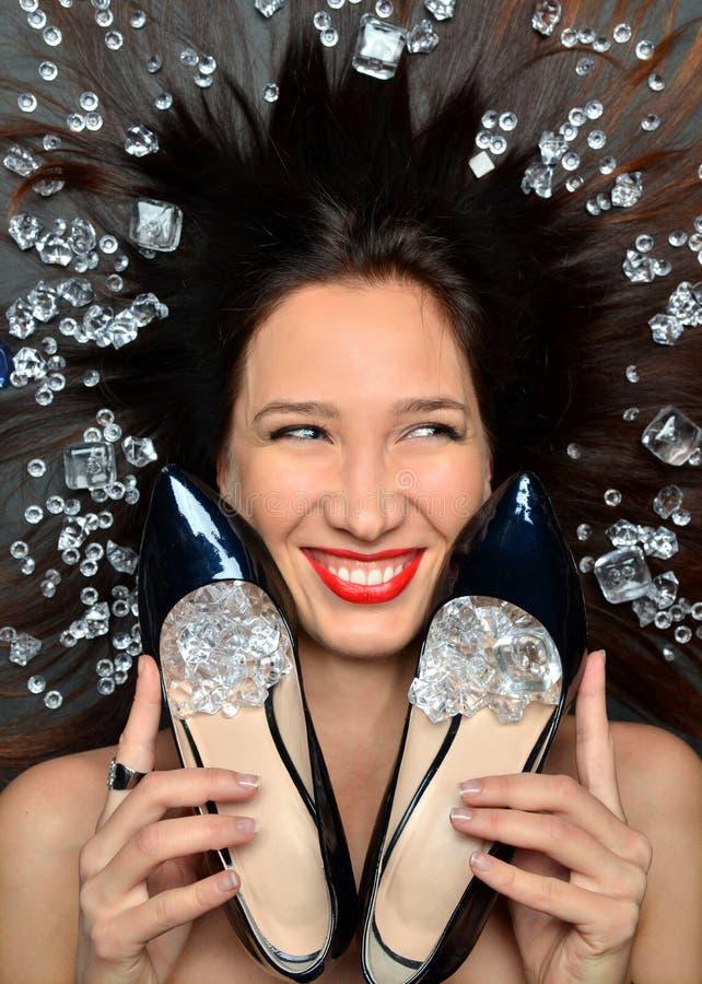 Il ritratto di una ragazza castana lussuosa si trova in un giacimento detritico dei gioielli dei diamanti, accessori di lusso immagini stock