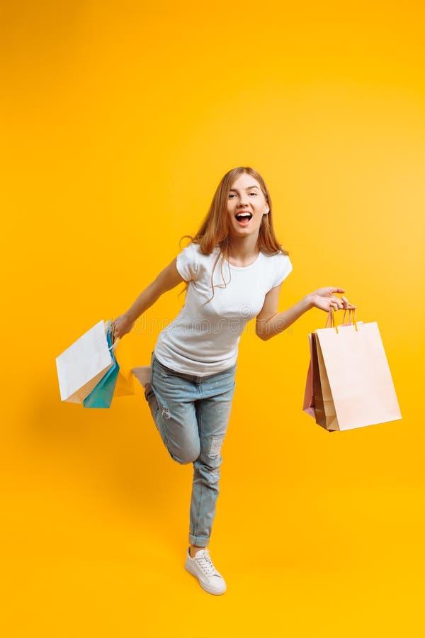 Il ritratto di una ragazza sorridente con le borse in sue mani, la ragazza ha fretta per la compera su un fondo giallo fotografie stock libere da diritti