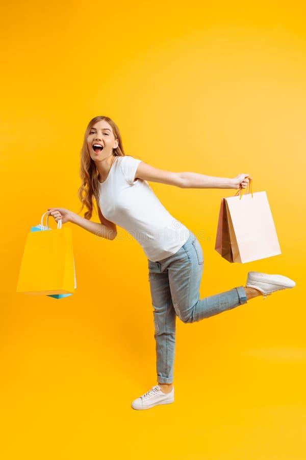 Il ritratto di una ragazza sorridente con le borse in sue mani, la ragazza ha fretta per la compera su un fondo giallo immagini stock
