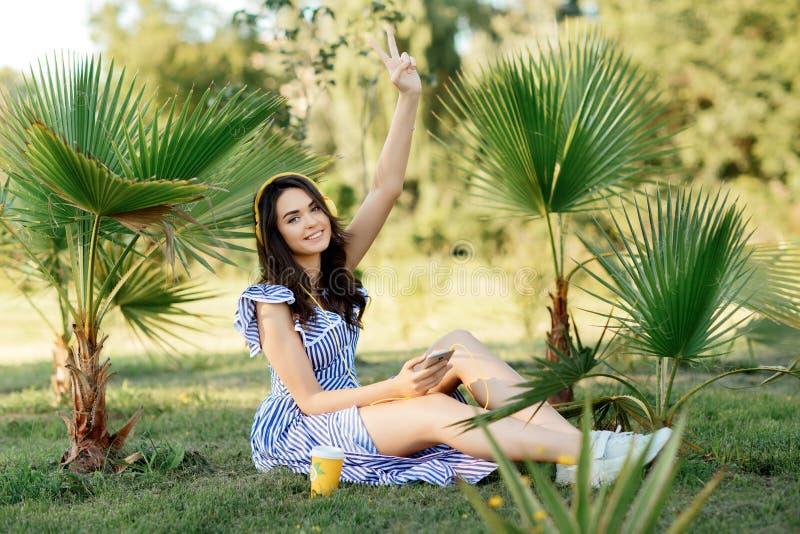 Il ritratto di una ragazza sorridente emozionante di estate copre ascoltare la musica con le cuffie mentre tiene il telefono cell fotografia stock