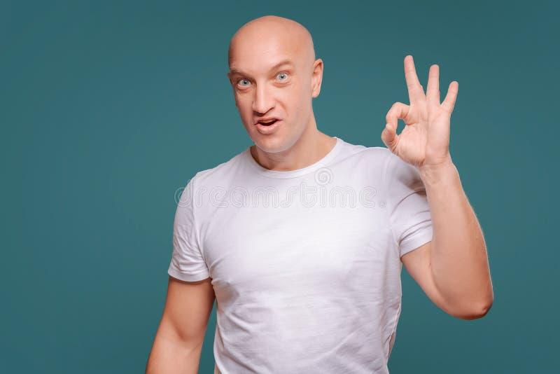 Il ritratto di una rappresentazione allegra dell'uomo approva il gesto isolato sui precedenti blu fotografie stock