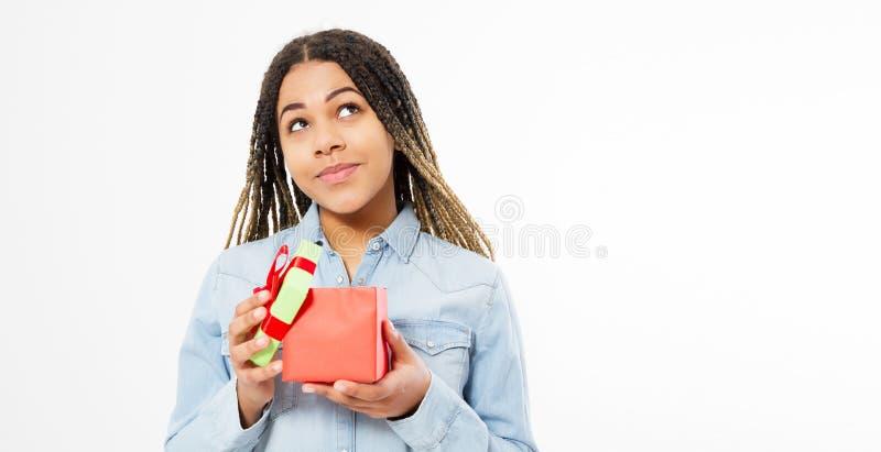 Il ritratto di una tenuta teenager sveglia emozionante della donna di colore ha aperto la scatola attuale isolata sopra fondo bia fotografia stock