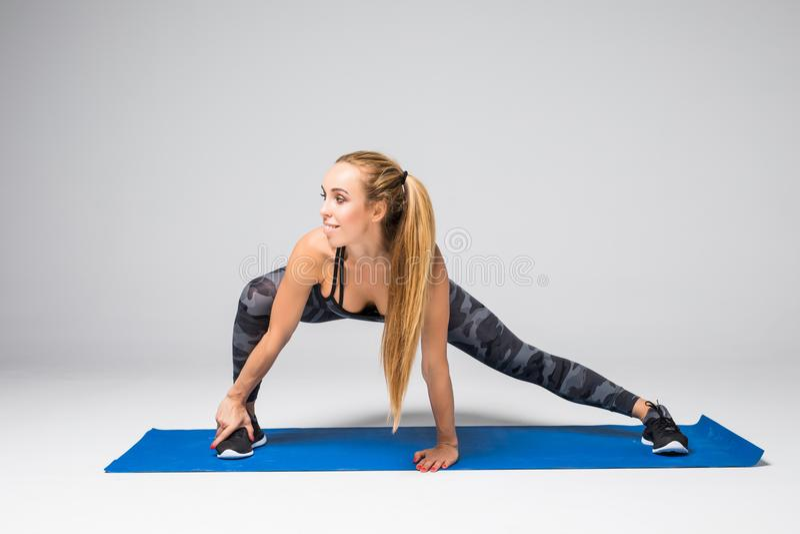Il ritratto di vista laterale di bella giovane donna che risolve contro la parete grigia, facendo l'yoga o i pilates si esercita  fotografia stock
