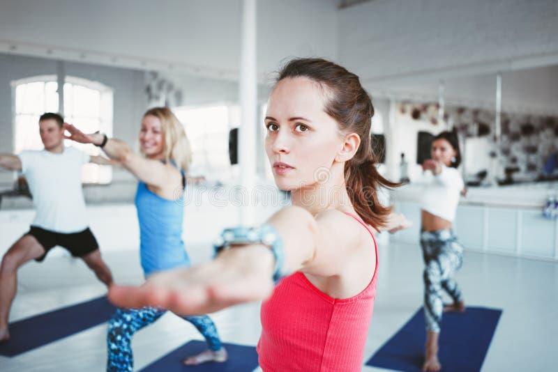 Il ritratto di yoga bella di pratica della donna esercita la palestra dell'interno del sottotetto con la gente del gruppo Ragazza immagine stock