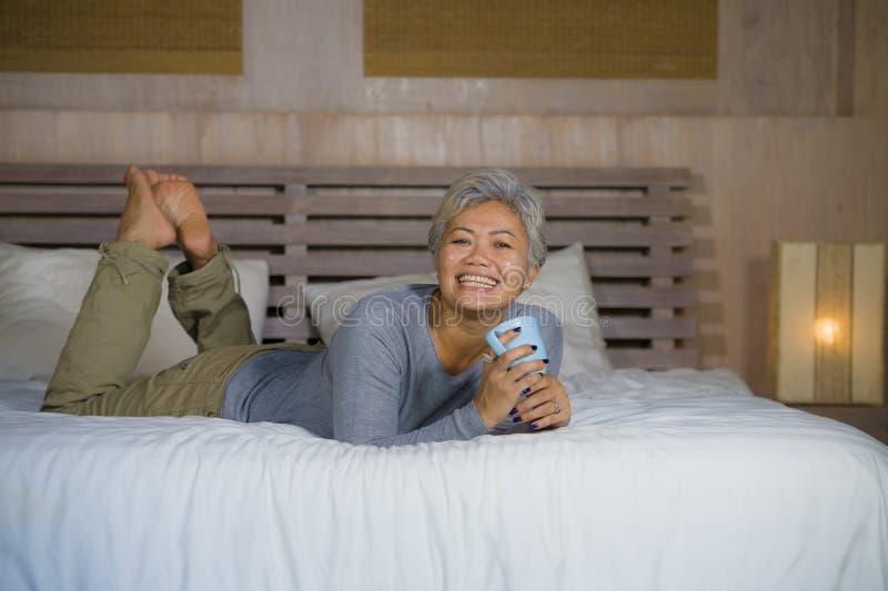 Il ritratto domestico della donna americana asiatica matura attraente e riuscita con capelli grigi che si siedono sul caff? beven immagini stock libere da diritti