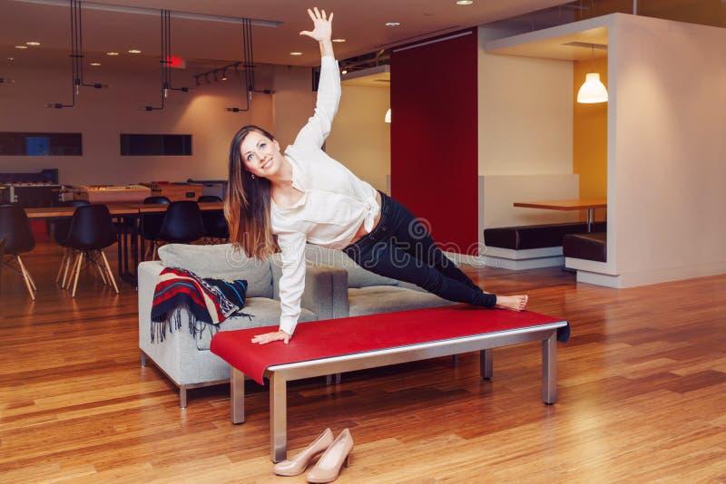 Il ritratto donna caucasica bianca sportiva di affari di misura esile di giovane che medita facendo l'yoga si esercita immagini stock