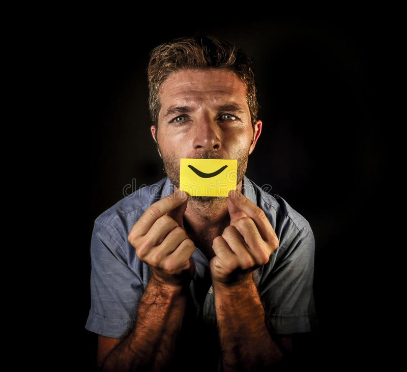 Il ritratto drammatico concettuale di giovane carta depressa della tenuta dell'uomo con la bocca sorridente felice attinge le sue fotografia stock libera da diritti