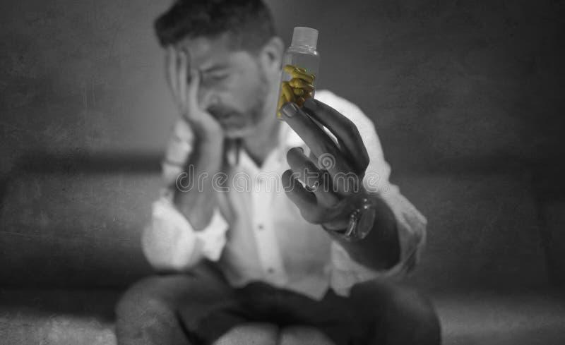 Il ritratto drammatico di giovani pillole depresse e sprecate attraenti si dedica l'uomo che tiene la bottiglia antidepressiva de fotografia stock libera da diritti