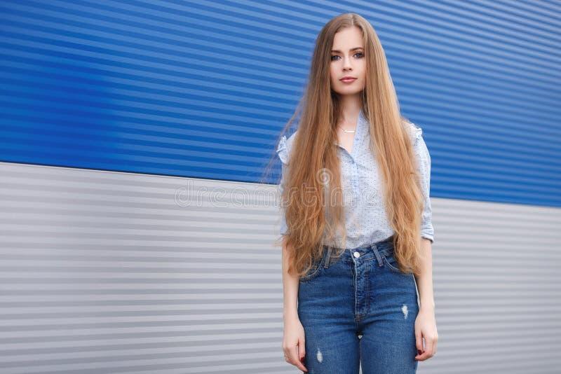 Il ritratto emozionale di una donna bionda graziosa adulta con capelli extra-lunghi splendidi che posano all'aperto contro il gre fotografia stock libera da diritti