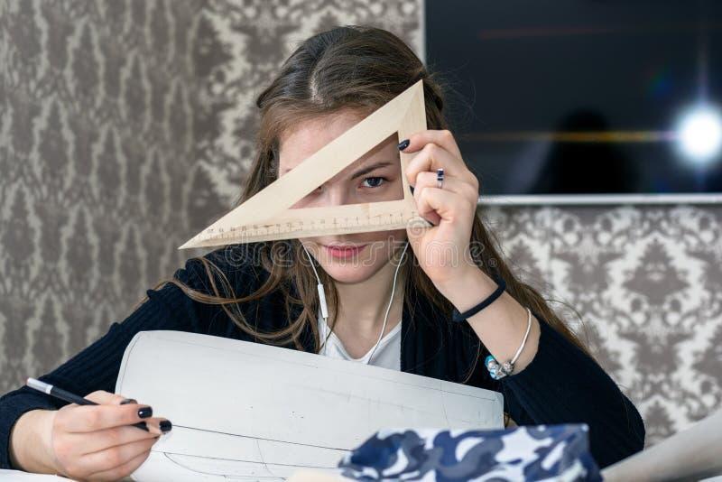 Il ritratto frontale di giovane studentessa è impegnato alla tavola disegna gli schizzi, gli schizzi, i piani, l'architettura add immagine stock libera da diritti